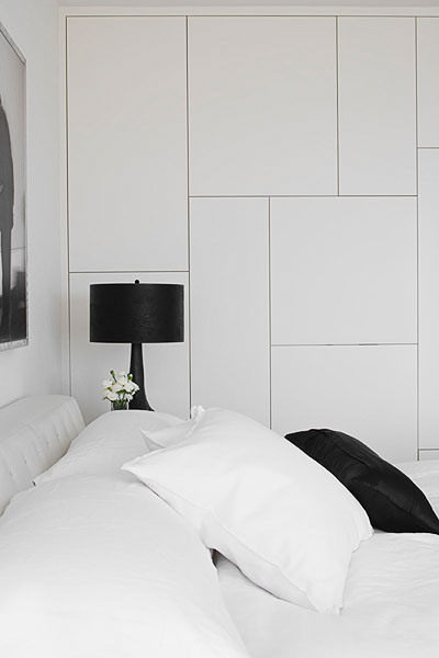 home, residential, bedroom, storage, white push-latch cabinets, bed, white bedding, black pillows, black faux hoofed lamps, modern