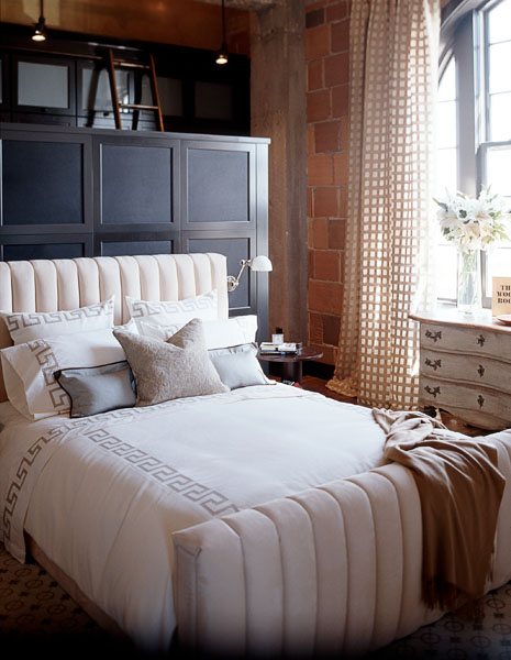 home, residential, bedroom, loft, exposed brick, floor to ceiling drapes, wood cabinets, warm white bedding