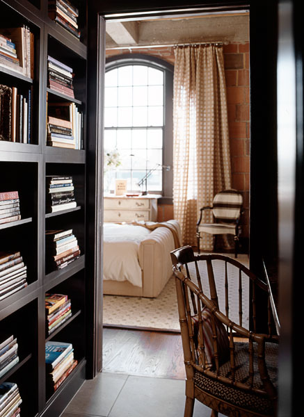 home, residential, bedroom, library, built in dark wood book shelves, floor to ceiling drapes, exposed brick, books