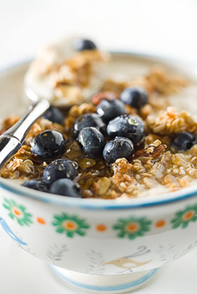 breakfast, granola, blueberries, milk, spoon, bowl with green and orange design