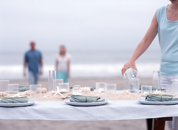 beach, outdoor dining, man, woman, couple, pouring, glasses, drinking, entertaining, blue shirt