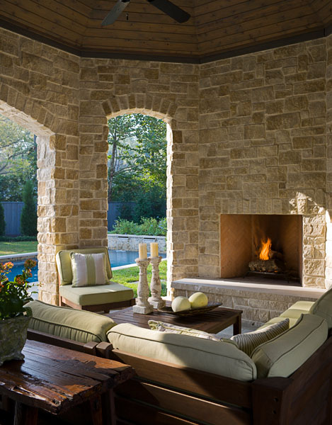 Residential, fireplace, stone, outdoor furniture, veranda, swimming pool in background, backyard