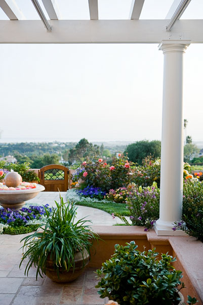 porch, deck, garden, plants, flowers, fountain, white column.