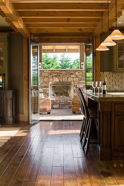 view from kitchen to deck, glass doors, residential, stone fireplace, wine, wood floor